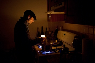 Brooklyn, NY - Nov. 7, 2012. Doug Zimmerman checks the level of water into two pots on the stove of the apartment he shares with a roommate in Coney Island - the water boiling on the stove serves as improvised heater. His apartment is in one of the buildings in the neighborhood that still lack electricity as aftermath of the passage of Hurricane Sandy, a week earlier. Today the apartment received power for the first time during three hours, then service got interrupted again. (Photo by Alessandro Vecchi)