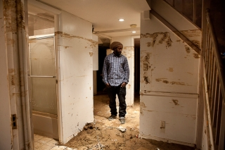 """Brooklyn, NY - Nov. 9, 2012. After showing to the photographer the level of damages of his girlfriend's basement apartment - which he cleaned out - in Canarsie, Yah-Yah Roby pauses and stares at the destruction caused by the passage of Hurricane Sandy, more than a week earlier. The water level reached 6'2"""". As of today, the heathing system and hot water do not work. (Photo by Alessandro Vecchi)"""
